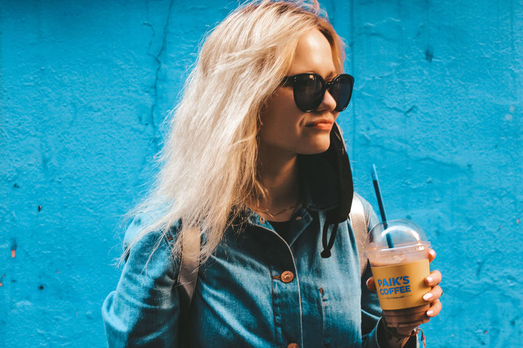 Young woman drinking water from sunglasses