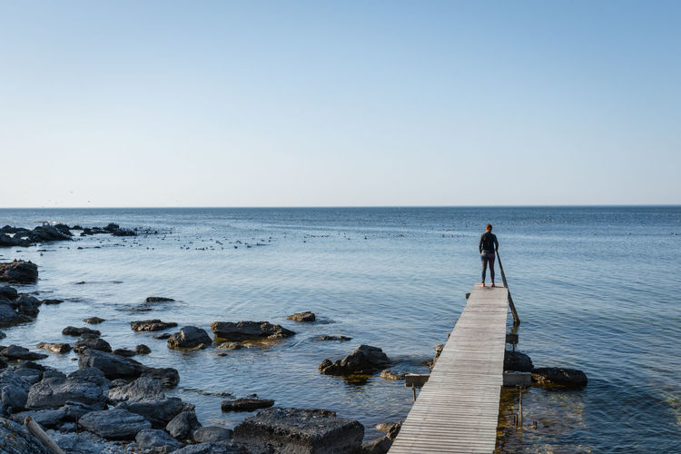 Rear view of man standing on pier by rocks by sea against sky