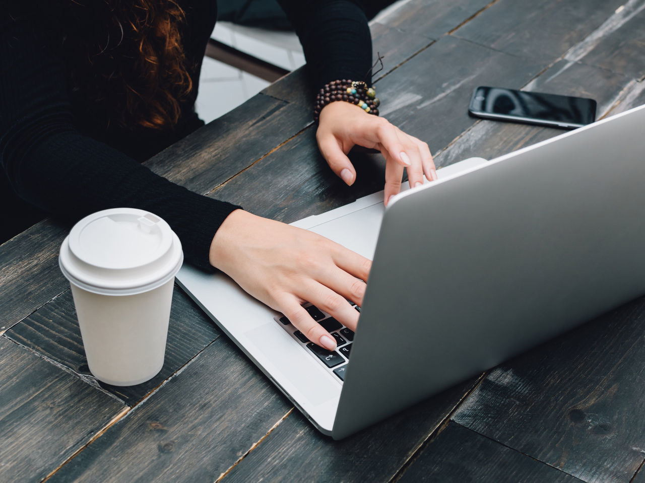 Midsection Of Woman Using Laptop At Table In Office