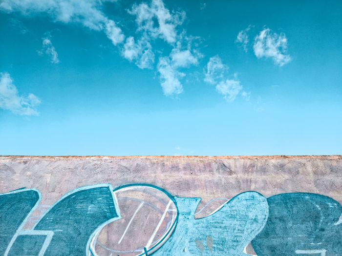 Low angle view of graffiti on wall against blue sky