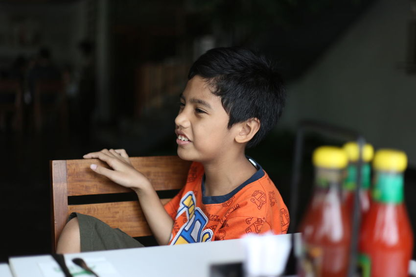 Side view of a Indonesian boy in a kitchen, having a fun chat with his mom (out of frame) 8 Years Old Child Childhood Children Only Fun Horizontal INDONESIA Indoors  Kitchen One Boy Only One Person People Photography Side View