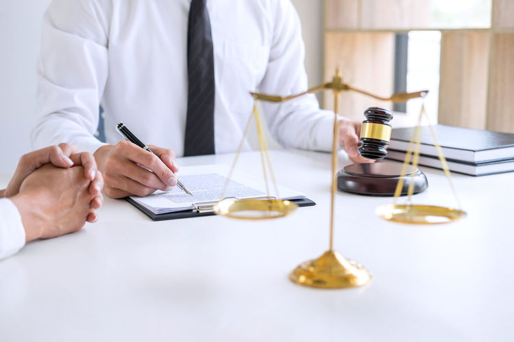 Midsection of lawyer reading contract for client at desk in office