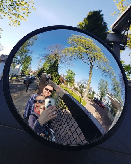 Happy young couple on side-view mirror against sky