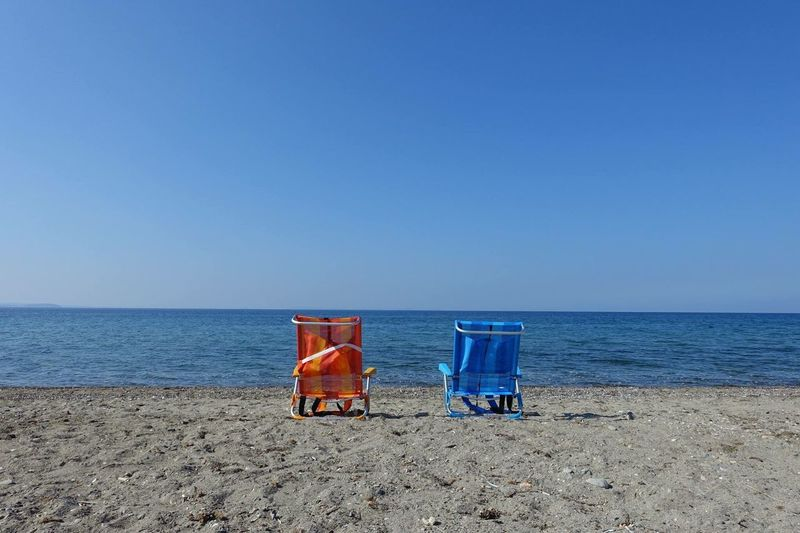Rear View Of Deck Chairs On Beach Against Clear Blue Sky