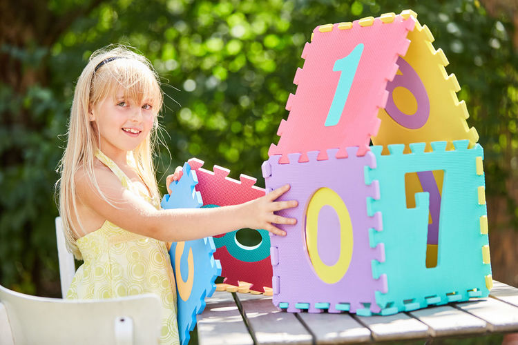 Portrait of girl with colorful model home at table in park