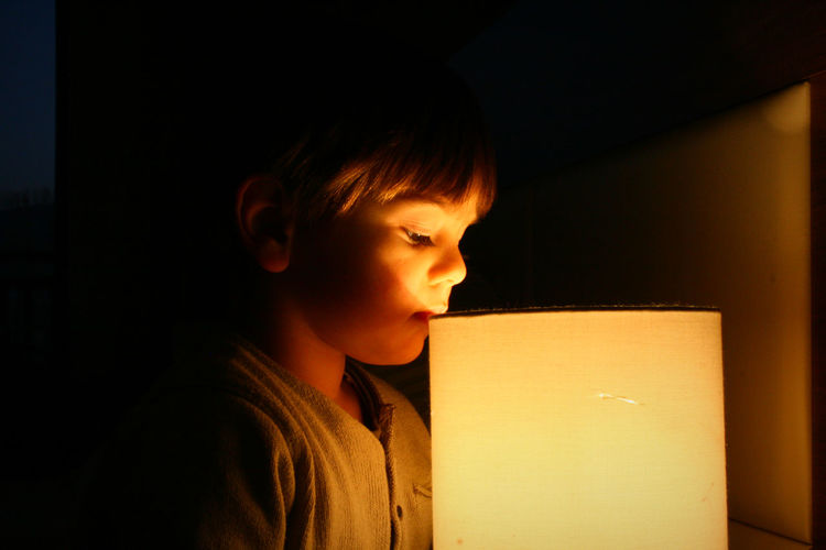 Close-Up Of Boy By Illuminated Lamp In Dark At Home