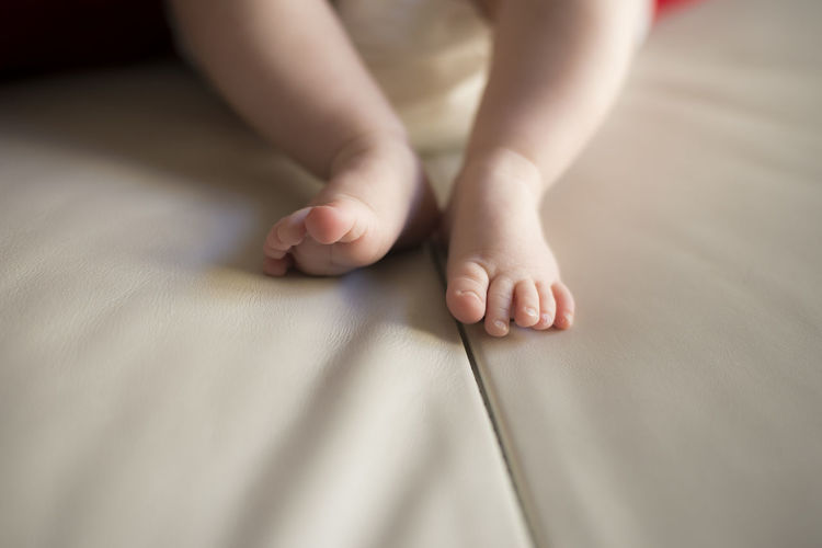 Low section of baby with bare feet on bed