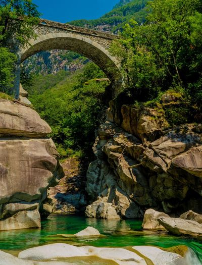 Arch bridge over river against rock formation