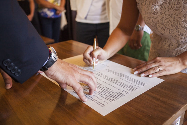 High Angle View Of Bride Signing Document On Table During Wedding
