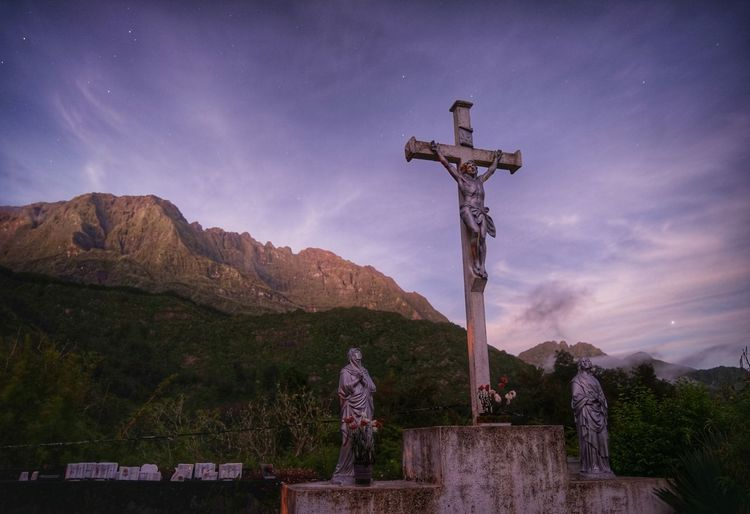 Cross and statues against sky
