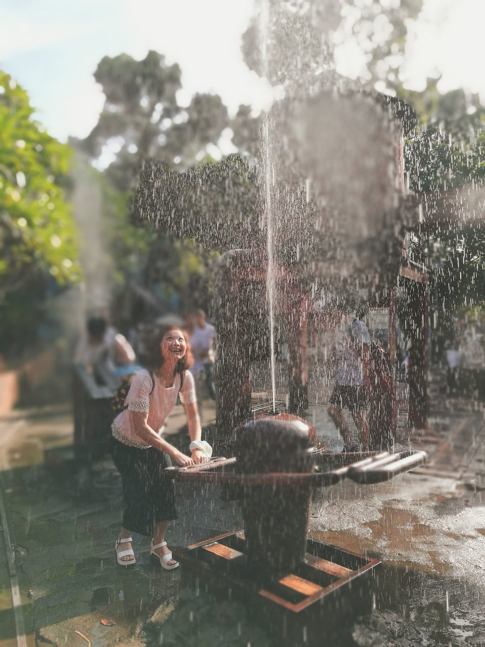 water, motion, fountain, splashing, spraying, wet, refreshment, real people, drop, leisure activity, day, outdoors, lifestyles, young women, happiness, fun, drinking fountain, young adult, full length, one person, tree, standing, nature, freshness, sky, people