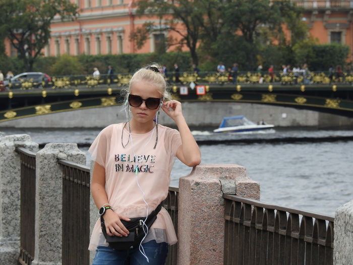 Portrait of girl wearing sunglasses while standing against canal in city