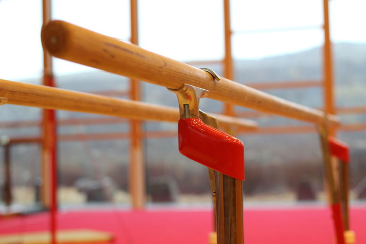 Close-up of red bell hanging on railing