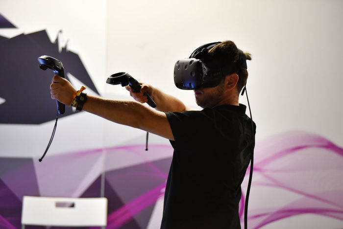 CLUJ-NAPOCA, ROMANIA - AUGUST 5, 2016: Boy tries virtual reality HTC Vive headset and hand controls during the virtual reality exposition, at the Untold Festival 3D Acitvity Console Device Entertainment Exhibition Experience Futuristic Garden Gay Headset I Landscape Mask Oculus Pavilion PC Plant Spftware Tachnology Te Videogame  Virtual Reality Virtual Web Museum Of Contemporary Art Vision
