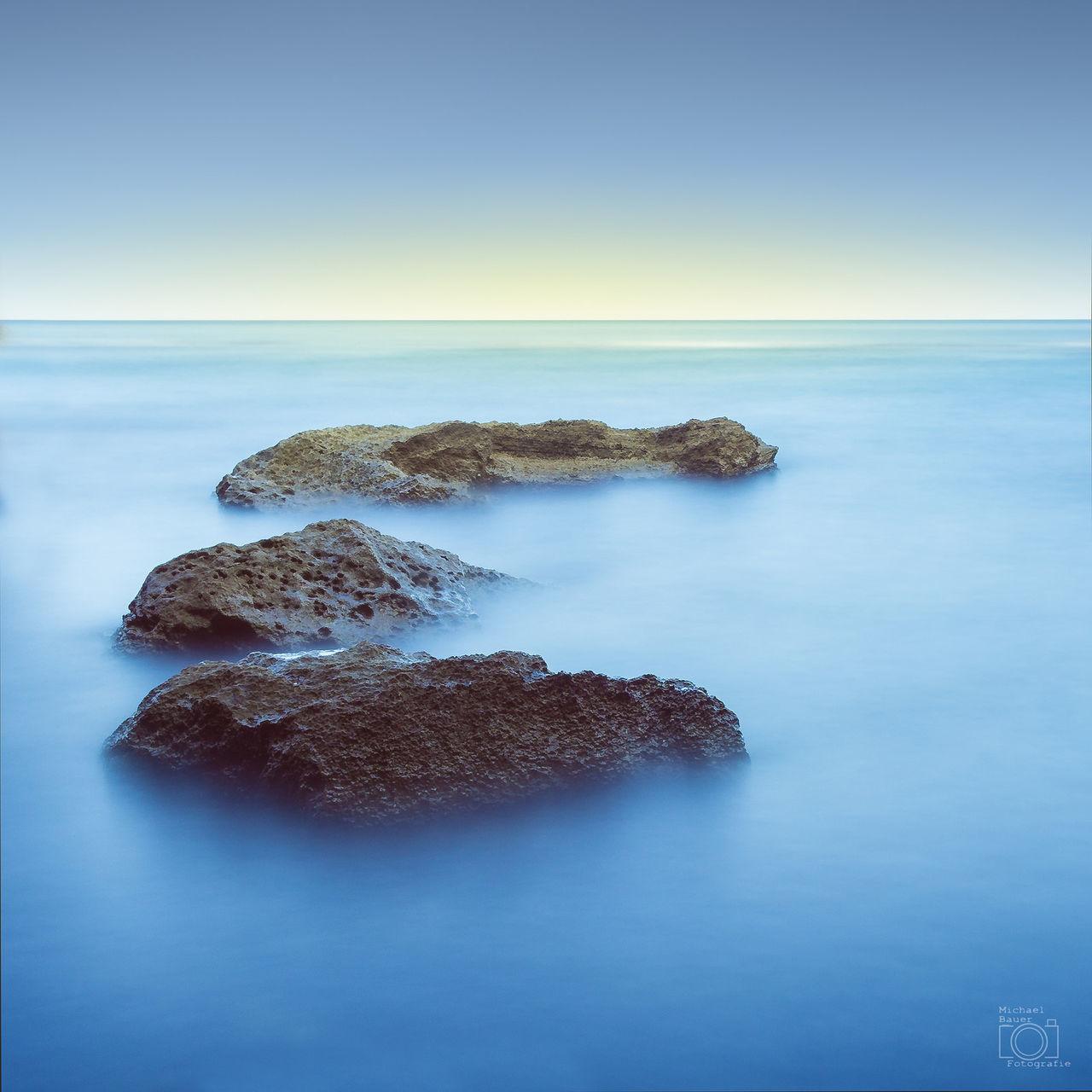 ROCK IN SEA AGAINST CLEAR BLUE SKY
