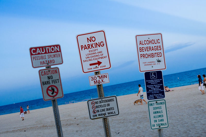 Signs at beach against sky