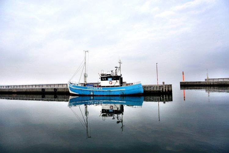 Trawler moored by piers over sea against cloudy sky