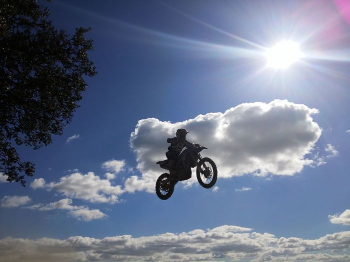 Low angle view of motocross racer performing mid-air stunt against sky