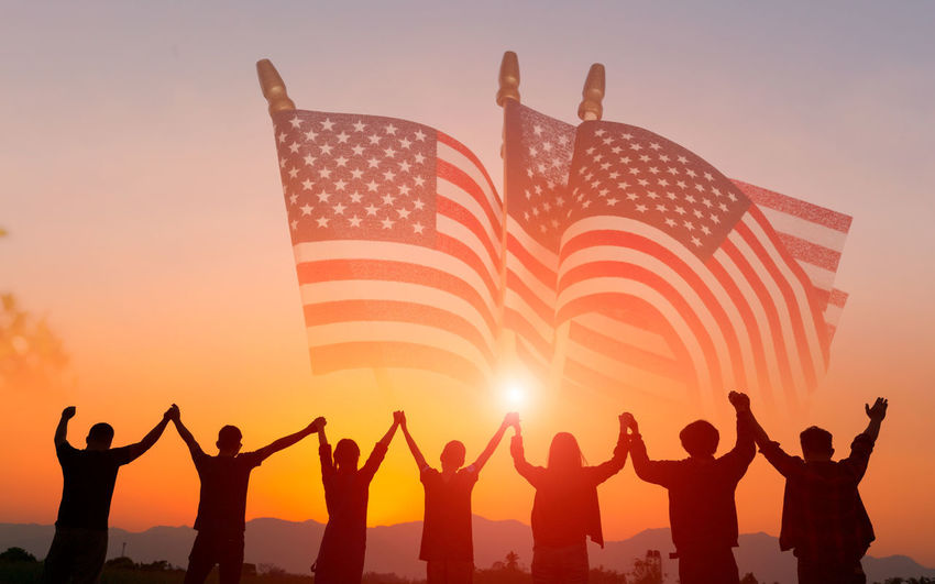 Red, white, and blue American flag on grass for Memorial Day or Veteran's day background Group Of People Sky Sunset Real People Men Human Arm Emotion Women Crowd Flag Patriotism Lifestyles Arms Raised People Togetherness Nature Leisure Activity Standing Adult Outdoors Hand Raised Excitement