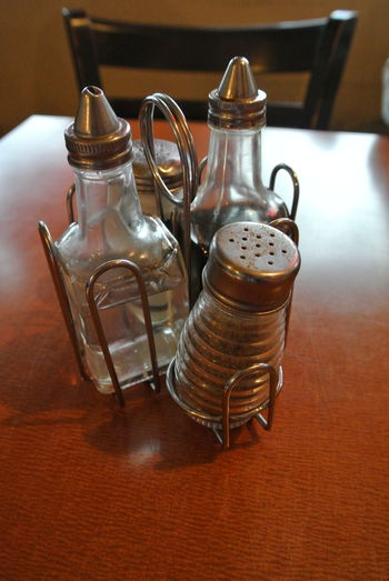 Close-up of bottles with pepper shaker on table