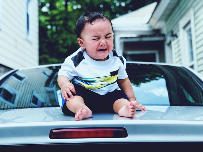 Full Length Of Baby Boy Crying While Sitting On Car