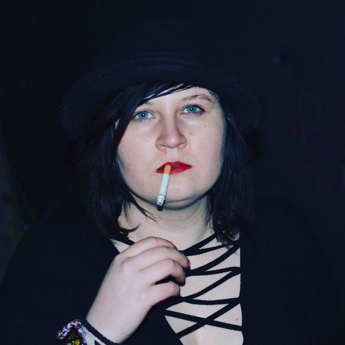 Close-up portrait of young woman smoking cigarette in darkroom