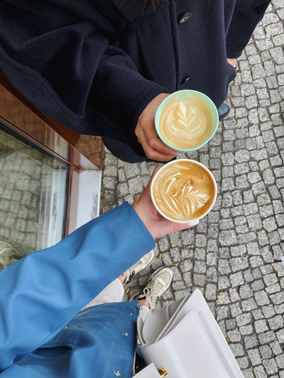 Low section of people holding coffee cup latte art