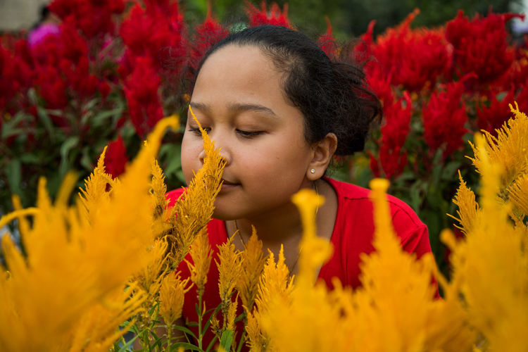 Close-up of girl smelling flowers on plants