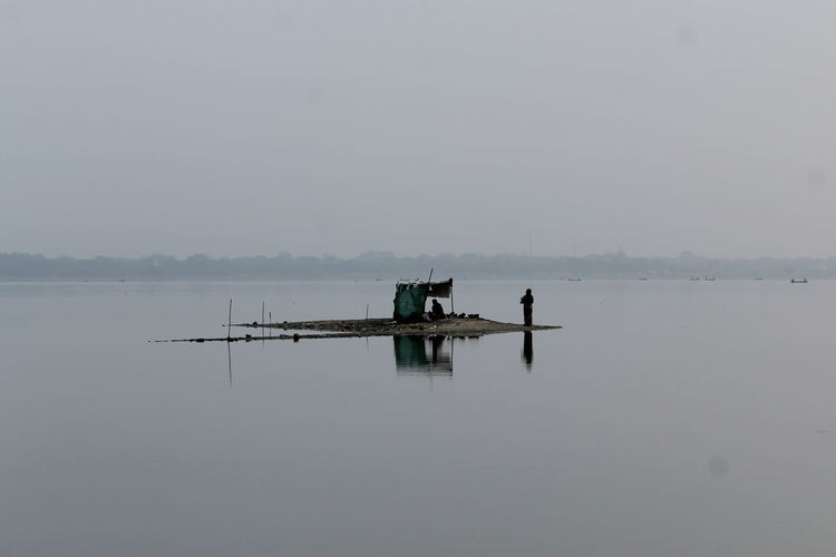 U-BEIN BRIDGE/AMARAPURA, MYANMAR JAN 22, 2016: A sandbank on Taungthaman Lake is being used for resting, shelter when raining and for breeding chicken. Amarapura Beauty In Nature Check This Out Day Fisherman Hazy  Lake Lifestock Mandalay Morning Myanmar Nature Outdoors Reflection Sandbanks Scenics Shelf Sky Sunset Tranquil Scene Tranquility Tranquility Transportation Water Waterfront An Eye For Travel