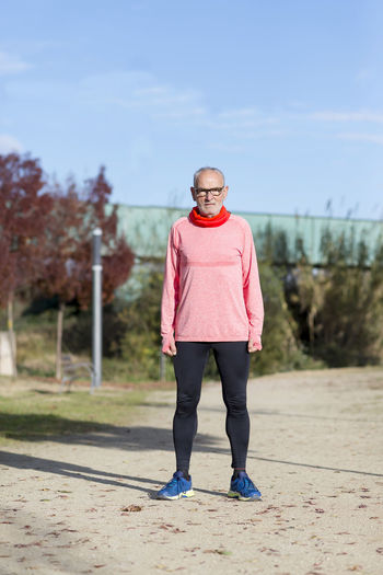 Senior man wearing glasses jogging at the park Casual Clothing Day Exercising Focus On Foreground Front View Full Length Leisure Activity Lifestyles Mature Women Nature One Person Outdoors Real People Sky Standing Tree Young Adult Young Women