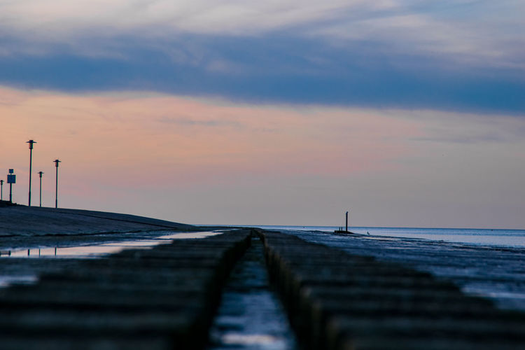 Surface level of pier against sky at sunset