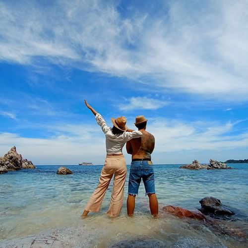 Rear view of men standing on rock by sea against sky