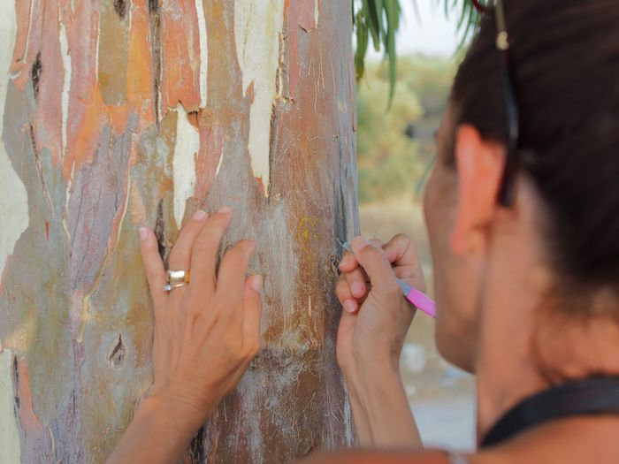 Close-Up Of Woman Making Heart Shape On Tree Trunk With Nail File