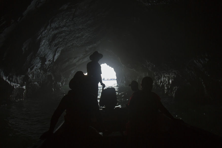 A group of tourists goes inside a cave near the beach. Pichilinguillo Beauty In Nature Cave Day Geology Indoors  Leisure Activity Lifestyles Men Nature People Physical Geography Real People Rock - Object Rock Formation Silhouette Stalactite  Togetherness Water Women An Eye For Travel