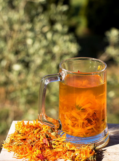 a large jar of marigold tea and dried flowers Beer Glass Close-up Drink Drinking Glass Dry Flower  Focus On Foreground Freshness Glass Glass - Material Healthy Hot Drink Household Equipment Marigold Marigold Flower Marigold Tea Medicinal Plant No People Non-alcoholic Beverage Outdoors Pitcher - Jug Refreshment Still Life Tea Tea - Hot Drink Transparent