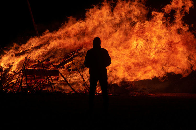 Fire Burning Fire - Natural Phenomenon Flame Heat - Temperature One Person Silhouette Standing Real People Nature Rear View Sign Men Orange Color Night Warning Sign Communication Accidents And Disasters Destruction Bonfire