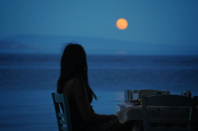 Side view of woman looking at sea against sky during dusk