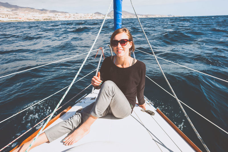 Portrait of smiling young woman sitting in boat on sea
