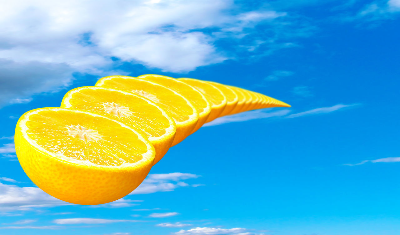 healthy eating, fruit, citrus fruit, food and drink, food, freshness, wellbeing, blue, cloud - sky, no people, orange, orange - fruit, orange color, close-up, sky, day, yellow, low angle view, slice, nature, blue background