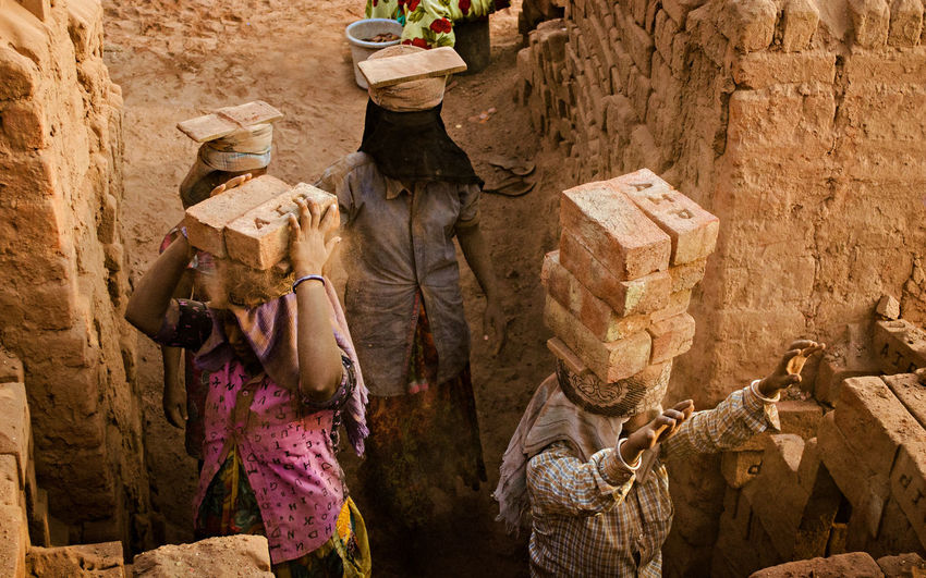 High angle view of manual workers carrying bricks at construction site