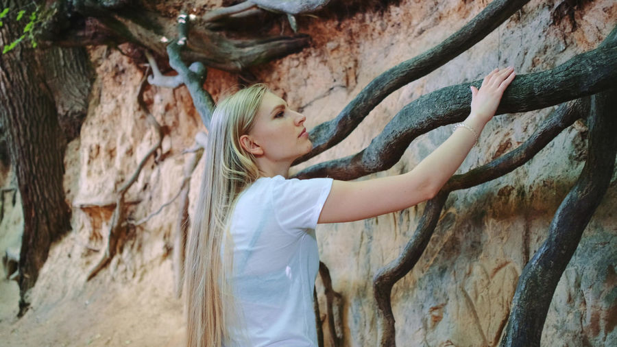Side view of young woman standing by tree trunk