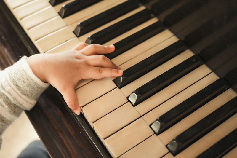 Cropped hand of baby playing piano