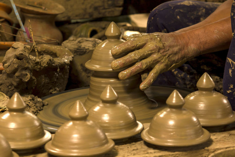 Making pottery using wet soil makes the shape of the container. Art And Craft Clay Craft Creativity Expertise Finger Hand Human Body Part Human Hand Indoors  Leisure Activity Making Molding A Shape Motion Mud Occupation One Person Pottery Pottery Art Pottery Bowls Pottery Making Real People Skill  Spinning