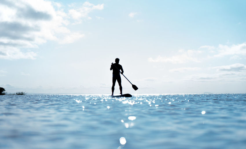 Silhouette Man Paddleboarding In Sea Against Sky