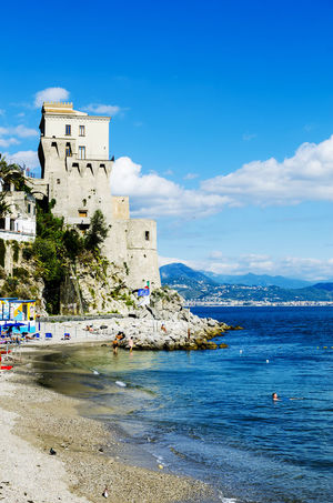 Cetara, Italy - October 2, 2013: Cetara small beach village on the Amalfi Coast, LA beach is defended by an ancient Saracen tower. Bathers on the beach on a warm October day. In the background you can see the city of Salerno Architecture Beauty In Nature Blue Building Exterior Built Structure City Cloud Cloud - Sky Coastline Day Lifestyles Nature Outdoors Scenics Sea Shore Sky Tourism Tourist Tranquil Scene Tranquility Travel Destinations Vacations Water