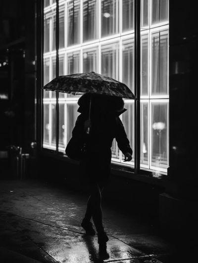 Full length of silhouette woman walking in rain