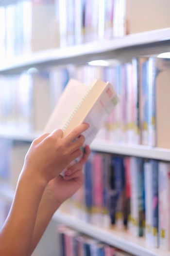 Cropped image of hand holding book in library