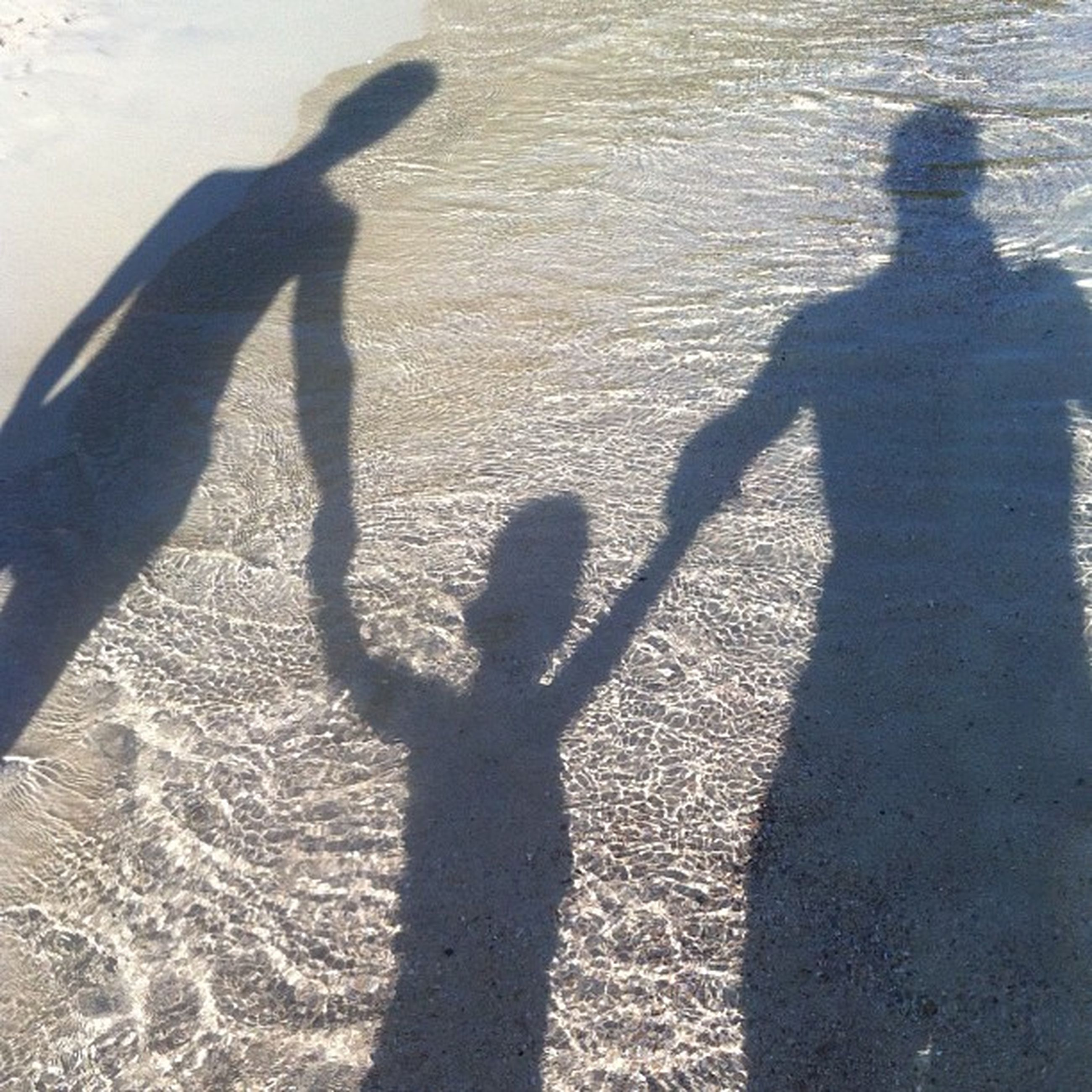 shadow, lifestyles, focus on shadow, sunlight, leisure activity, high angle view, men, standing, togetherness, walking, sand, day, street, unrecognizable person, bonding, outdoors, low section