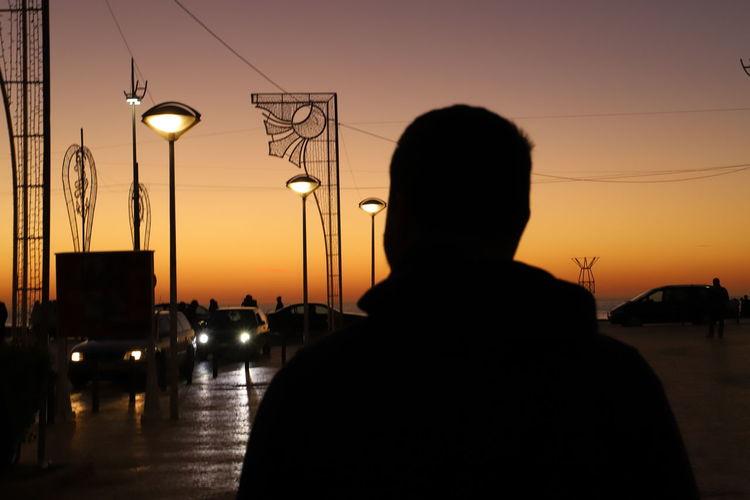 Silhouette man and illuminated street light against orange sky