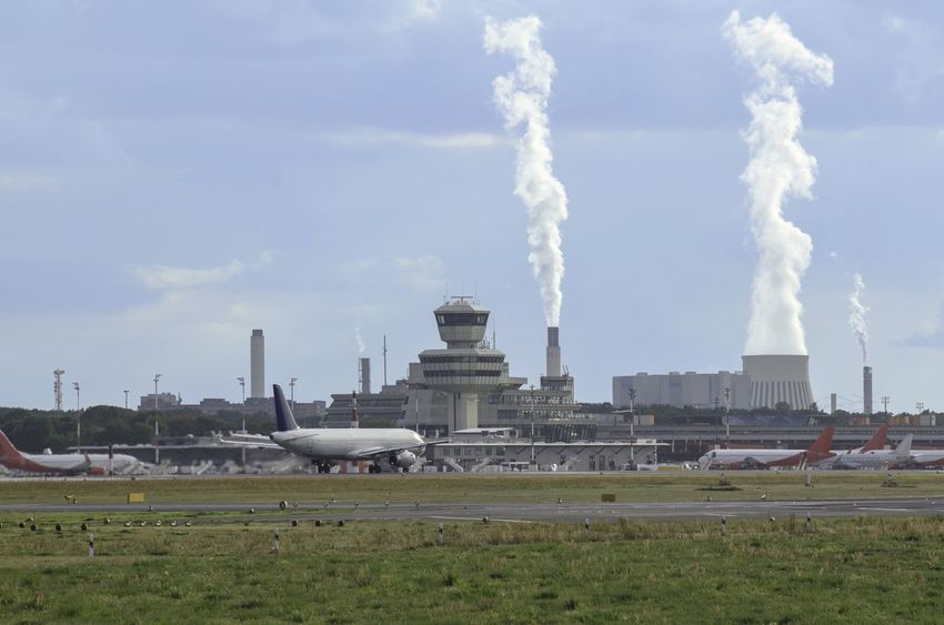 Airplanes parked at Tegel airport in Berlin. Behind, smoke coming from factories' chimneys Control Tower Tower Airport Planes Buildings Terminal Chimneys Fume Smoke Sky Blue Sunny Outdoors Travelling Holidays Business Aviation Waiting Vacations